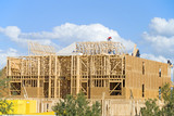Three story frame condos under construction and a clear day poster