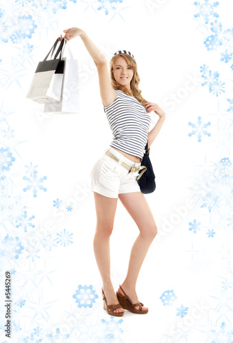 cheerful blond with shopping bags and snowflakes