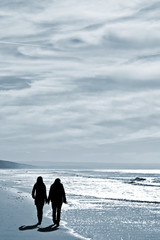 two women walking at the beach in the winter