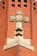 Stone Cross Against Red Brick