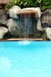 Leinwanddruck Bild - Man-made waterfall flowing into a swimming pool