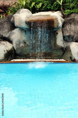 Leinwanddruck Bild Man-made waterfall flowing into a swimming pool