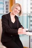 smiling businesswomen writing in a calendar poster
