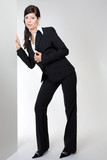 Office Mädchen in Anzug an Wand horchend poster