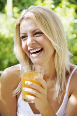 happy woman drinking her morning orange juice in her garden