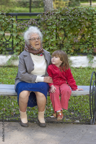Great Grandmother holding grandchild sitting on the bench