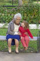 Great Grandmother talking to grandchild sitting on the bench