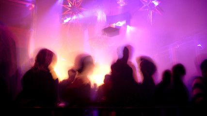Nightclub scene with dance floor crowd in motion