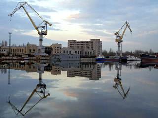 Shipyard view with two cranes reflection on water