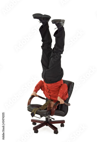 Businessman relaxing, standing on his head - isolated
