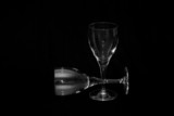 thin wine glasses againt a black background, one laying down poster