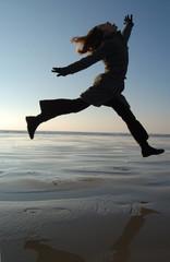 jeune fille sautant sur la plage