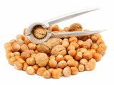 Walnuts and hazelnuts with nutcracker isolated over white poster