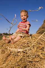 barefooted baby boy sit on a hayrick and play tricks