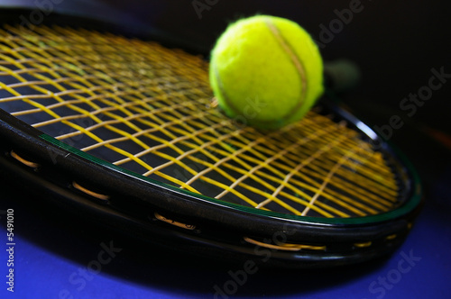 Closeup of a tennis racket and ball