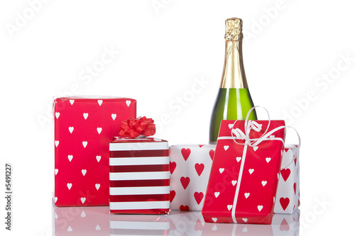 Gifts and champagne, reflected on white background. Shallow DOF