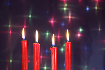 four Christmas  red candles against glow backdrop