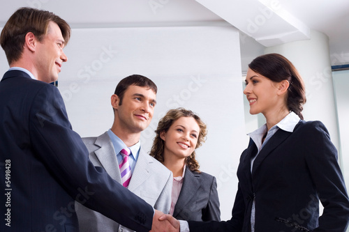 Image of businessman and woman shaking hands at meeting