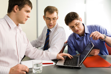 Group of three business men interacting in the office