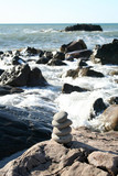 stack of stones built on a rocky coastline. poster