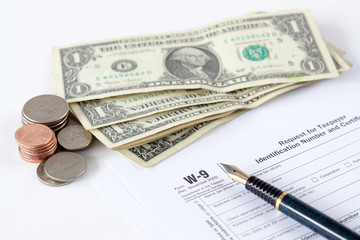 W-9 income tax form with pen and american dollars