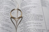 A wedding ring on a bible open to marriage scripture. poster