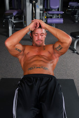 A bodybuilder in the gym doing sit ups