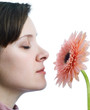 Girl on white background smelling pink flower