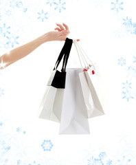 hand with three shopping bags and snowflakes