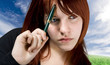 Cute girl with red hair holding a pen against her forehead