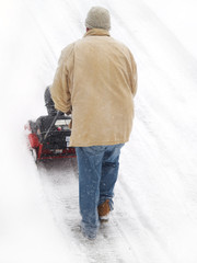 man using a snow blower on in winter