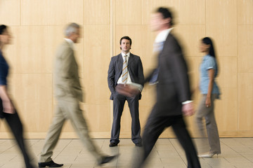 Confident businessman with team walking past him