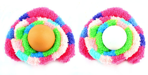two eggs in a multicolored fluffy easter clutches