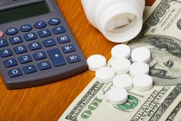 Open bottle of pills on top of money