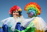 Two bizzare clowns in colored wigs upon blue sky poster