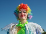 Expressive bizzare clown in colored wig upon blue sky poster