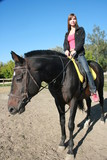 female equestrian in saddle of black stallion poster