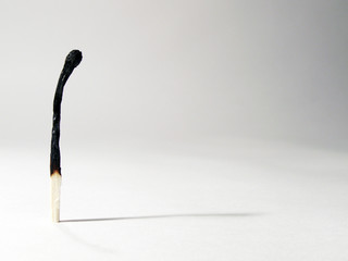 Lonely burnt match standing with its shadow
