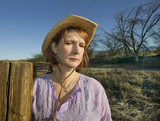 Portrait of a woman in a purple shirt and cowboy hat on a ranch. poster