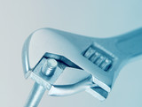 Close-up of adjustable spanner gripping a nut and bold poster
