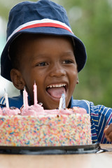 African American boy next to his birthday cake