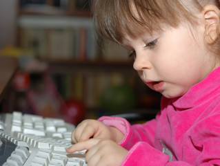 The little girl for studying keyboard of a computer