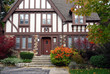 tudor style home with brown trim and sumac bush in fall