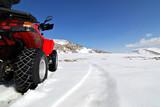 Fototapety red quad bike in snow mountain scenery