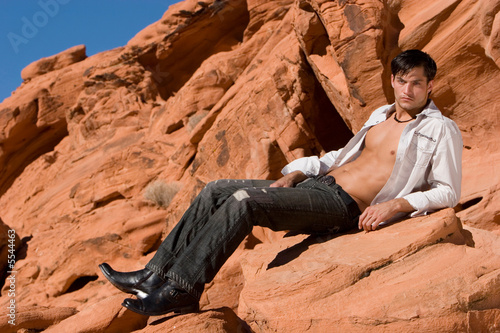 Sexy young man on red rocks