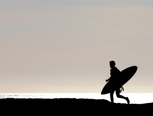 Surfer silhouetted while running along cliff