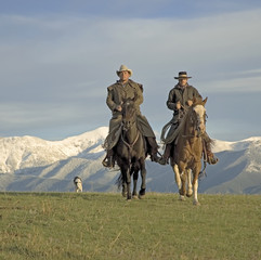 Cowboys on the range, mountain backdrop.