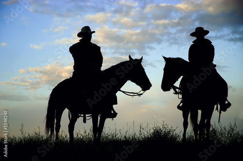 Cowboys on a Montana ridge at dawn, back lit by the rising sun