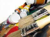 Paint brushes on palette with paint tubes poster