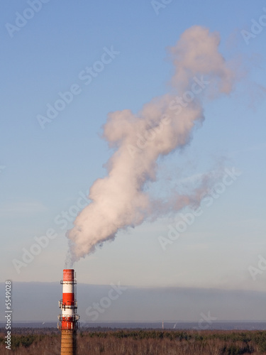 Stand-alone red-white boiler-house chimney smoking